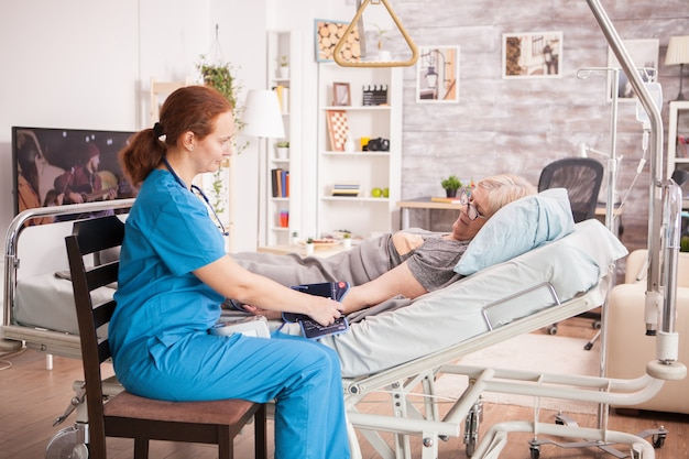 ベッドに横たわっている年配の女性の血圧をチェックする女性医師。老人ホーム。