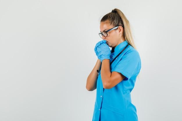 青い制服を着て祈るジェスチャーで手を握り締める女医師