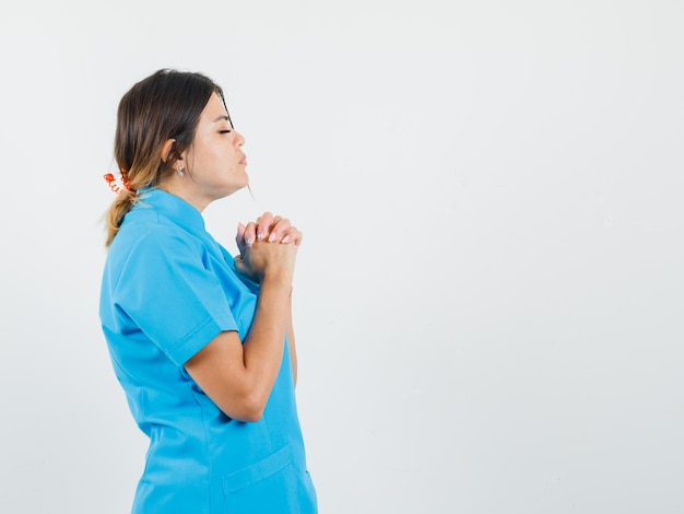 Female doctor clasping hands in praying gesture in blue uniform and looking calm