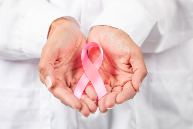 Female doctor closeup on hands holding breast cancer awareness ribbon.