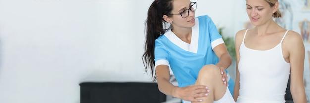 女医が患者の膝関節の身体検査を行う