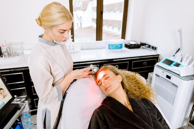 여성 의사는 얼굴 피부를 젊어지게하는 절차를 수행합니다. 얼굴 치료를 받고, 클리닉에서 색소를 제거하는 아름 다운 금발 여자.