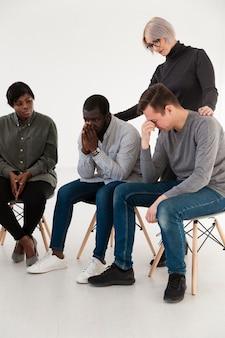 Female doctor consoling sad men