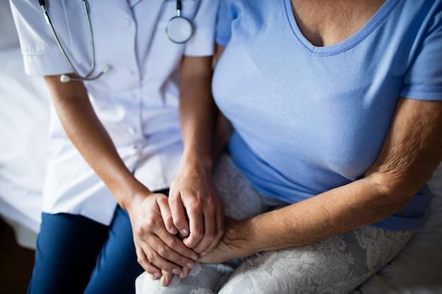 寝室で年配の女性を慰める女医