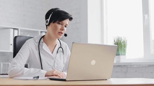 Женщина-врач консультирует пациента удаленно онлайн с помощью веб-камеры на ноутбуке
