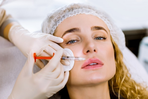 Female doctor cosmetologist in white rubber gloves makes lip augmentation procedure of a beautiful woman in modern beauty salon.