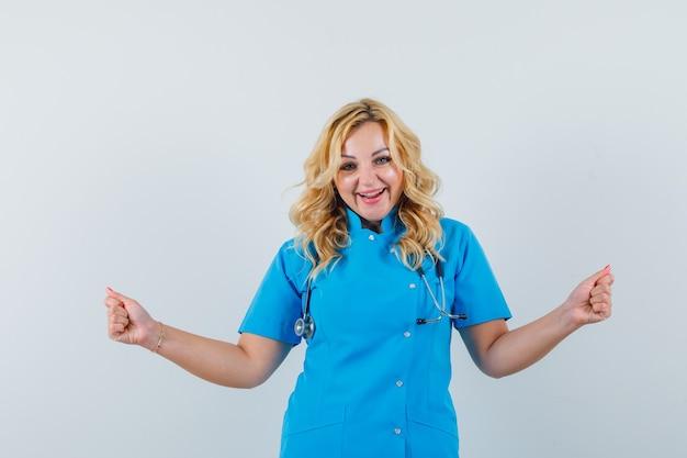 Женщина-врач танцует в синей форме и выглядит удивленно