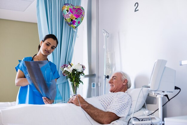 病棟の男性上級患者とx線レポートを議論する女性医師