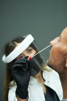 男性患者に鼻咽頭スワブテストを行う女性医師。医療用保護具のマスク、保護メガネ、手袋、スモックを着用している医師。
