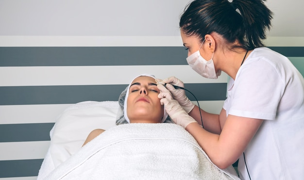 Женщина-врач делает радиочастотный подъем женщине в клинике