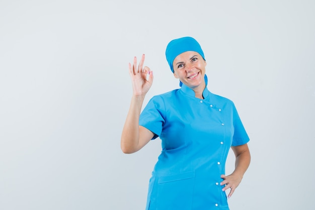 Medico femminile che fa gesto giusto in uniforme blu e che sembra fiducioso, vista frontale.