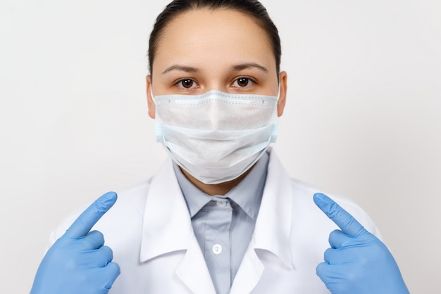 A female doctor in a dressing gown and gloves points with her hands at a protective respiratory mask