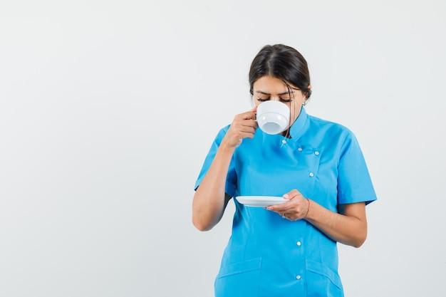 파란색 유니폼에 향기로운 차를 마시고 기쁘게 찾고 여성 의사