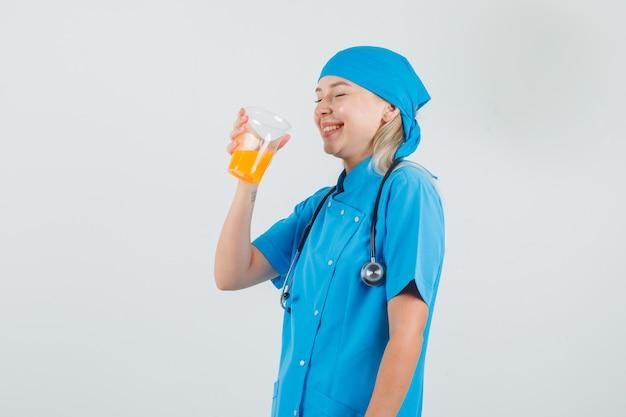 フルーツジュースを飲み、青い制服を着て笑う女医師