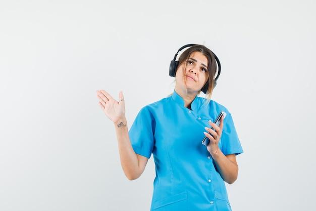 青い制服を着た携帯電話を持って、ヘッドフォンで音楽を楽しむ女性医師