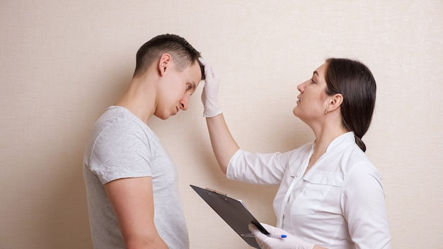 여성 의사는 남성의 머리를 검사하고 문서를 작성하고 기억상실증을 복용합니다