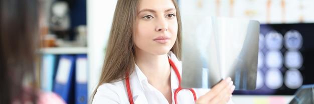 Женщина-врач изучает рентгеновский снимок пациентов на стойке регистрации