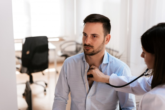 Female doctor examines a young man colds