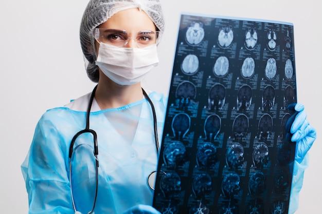 女医が彼女のオフィスで患者の脳のmriを調べる