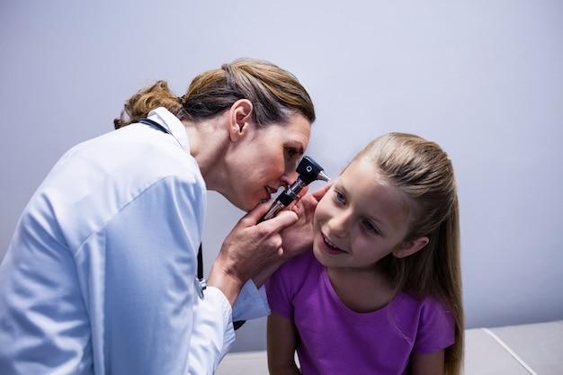 女医が耳鏡で患者の耳を調べる