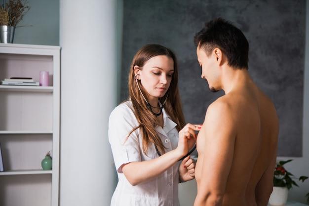 クリニックの医療キャビネットで聴診器で患者を診察する女性医師。ヘルスケアと医師の概念