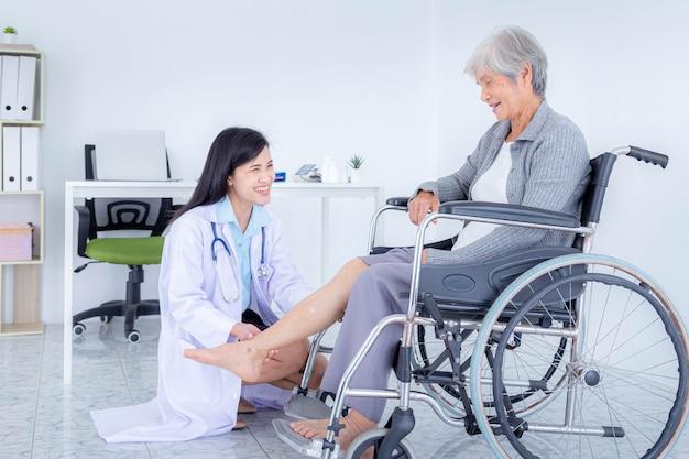여성 의사는 휠체어에 앉아 있는 동안 고위 여성의 다리를 검사합니다. 노인 환자 치료 및 건강 관리, 의료 개념.