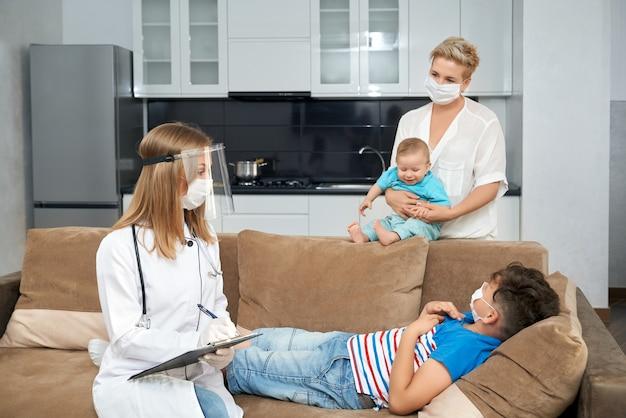 집에서 아픈 십 대를 검사하는 여성 의사