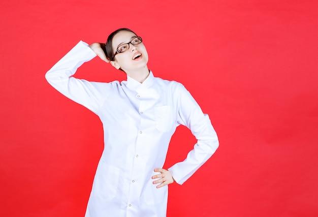Dottoressa in occhiali in piedi su sfondo rosso e sentirsi positiva e gioiosa.