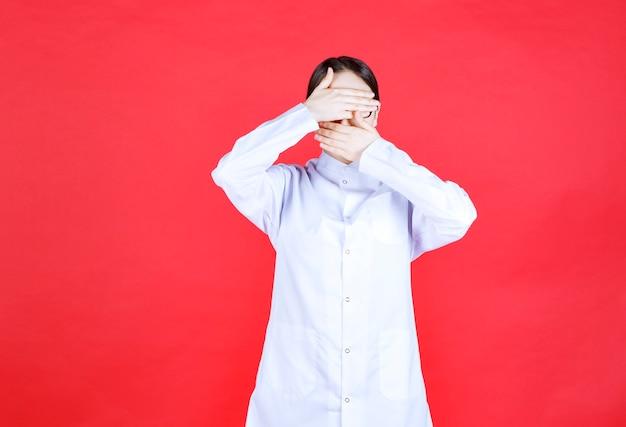 Dottoressa in occhiali in piedi su sfondo rosso e sentirsi stanca e assonnata.