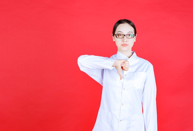 Dottoressa in occhiali in piedi su sfondo rosso e mostrando il pollice verso il basso.
