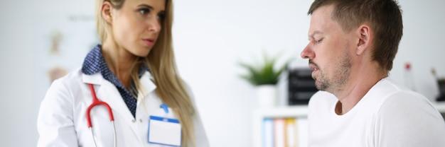 女性医師が患者の膝にキネシオテープを固定する