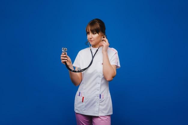 여성 의사는 청진기를 사용하여 병원의 의사 사무실에서 심장 박동을 확인하고 흰색 배경에 격리합니다. 환자를 치료할 준비가 된 의사. 의사는 행복으로 그녀의 직업을 사랑합니다
