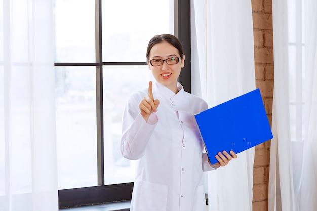 Female doctor in glasses holding blue folder near window.