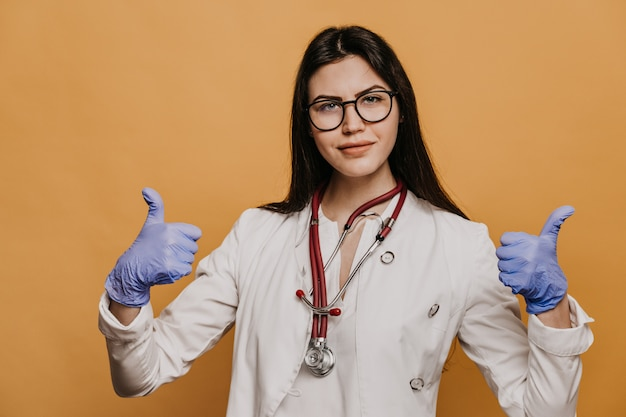 Female doctor in glasses, phonendoscope on her neck dressed in a medical gown, shows thumb up gesture.
