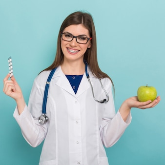 Female doctor in glasses with apple and pills