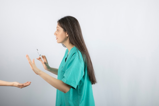 Female doctor in green uniform getting shot on white.