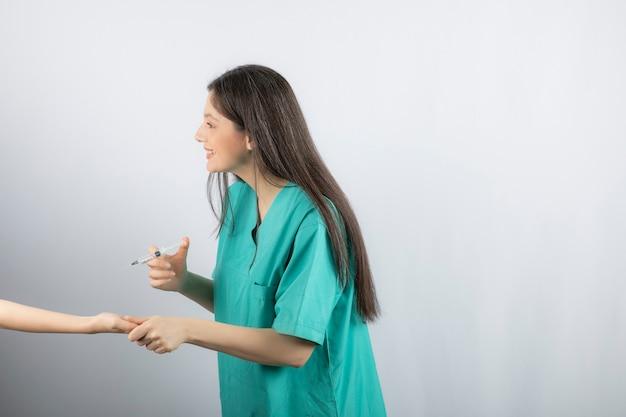 Medico femminile in uniforme verde che ottiene sparato su bianco.