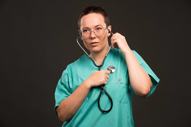 Female doctor in green uniform holding a stethoscope and checking her heartbeats.