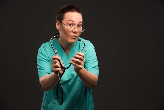 Female doctor in green uniform holding a stethoscope and checking.