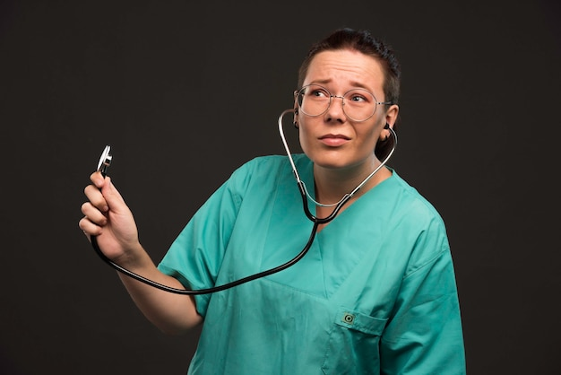 Female doctor in green uniform holding a stethoscope and listening the patient.