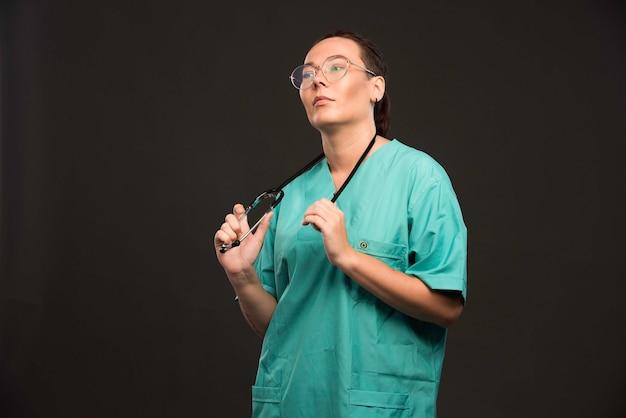 Medico femminile in uniforme verde che tiene uno stetoscopio e sembra sicuro.