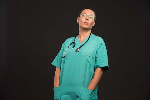 Female doctor in green uniform holding a stethoscope and looks confident.
