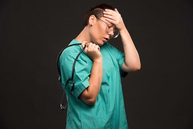 Medico femminile in uniforme verde che tiene uno stetoscopio e sembra stanco.