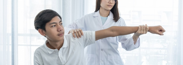 Female doctor hand doing physical therapy by extending the hand of a male patient.