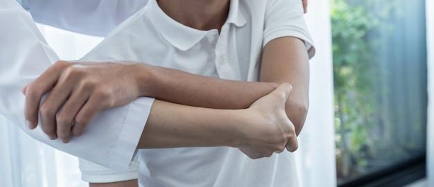남성 환자의 어깨를 확장하여 물리 치료를 하는 여성 의사의 손.