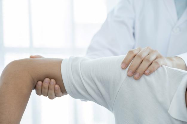 Женщина-врач рука делает физиотерапию, расширяя плечо пациента мужского пола.