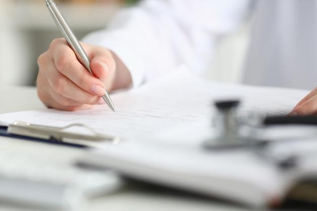 女医の手が患者の病歴リストを満たす銀のペンを保持する