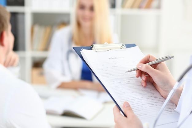 Женский доктор рука держать серебряную ручку заполнение списка пациентов