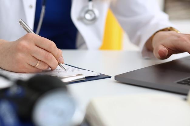 Женский доктор рука держать серебряную ручку наполнения пациента
