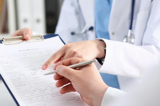 여성 의사 손 보유 실버 펜 및 표시 패드.